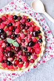 Pizza pie with mascarpone cream cheese, raspberry, black currant, strawberry, cherry on a wooden table. Homemade pie. Fruit pizza. Picnic food. Easter food royalty free stock image