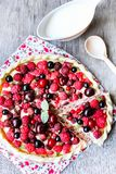 Pizza pie with mascarpone cream cheese, raspberry, black currant, strawberry, cherry on a wooden table. Homemade pie. Fruit pizza. stock photography