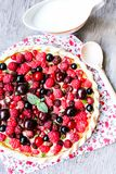 Pizza pie with mascarpone cream cheese, raspberry, black currant, strawberry, cherry on a wooden table. Homemade pie. Fruit pizza. Picnic food. Easter food royalty free stock photo