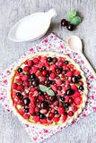Pizza pie with mascarpone cream cheese, raspberry, black currant, strawberry, cherry on a wooden table. Homemade pie. Fruit pizza. royalty free stock photography