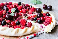 Pizza pie with mascarpone cream cheese, raspberry, black currant, strawberry, cherry on a wooden table. Homemade pie. Fruit pizza. Picnic food. Easter food stock photography