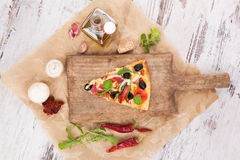 Pizza piece and pizza ingredients. Royalty Free Stock Image