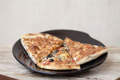 Pizza pieces. On plate and on table Royalty Free Stock Photography