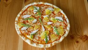 Pizza with pineapple and chicken spinning in a circle. Fast food. View from above stock video