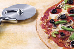 Pizza and pizza cutter Royalty Free Stock Photography