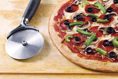 Pizza with pizza cutter Royalty Free Stock Photography