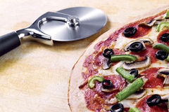 Pizza with pizza slicer Royalty Free Stock Images