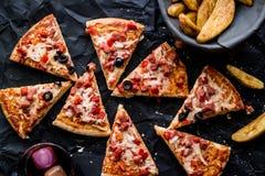 Pizza plasterki z grula klinami i napój na czarnej powierzchni & x28; Fasta food concept& x29; Zdjęcie Royalty Free