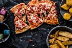 Pizza plasterki z klinami, bryłkami i napojem na czarnej powierzchni gruli, & x28; Fasta food concept& x29; Obraz Stock