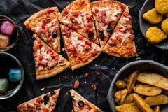 Pizza plasterki z klinami, bryłkami i napojem na czarnej powierzchni gruli, & x28; Fasta food concept& x29; Zdjęcia Royalty Free