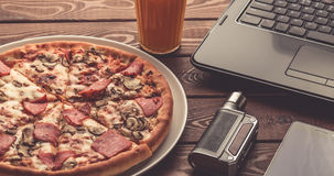 Pizza on a plate, black laptop, electronic cigarette or vape, mobile phone and a glass of fruit juice on wooden table. Business lunch concept royalty free stock photography