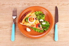 Pizza on plate and knife with fork on wooden Royalty Free Stock Images