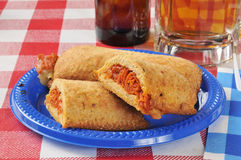 Pizza pockets. Stuffed with italian meats on a picnic table with beer Royalty Free Stock Photography