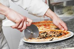 Pizza preparartion - cutting Stock Image
