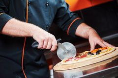 Pizza preparartion - cutting Royalty Free Stock Photo