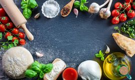 Pizza Preparation With Ingredients On Black Table Stock Images