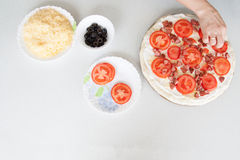 Pizza preparation surrounded by ingredients Stock Images