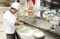 Pizza preparing in kitchen. A chef is preparing pizza in a restaurant's kitchen Royalty Free Stock Photo
