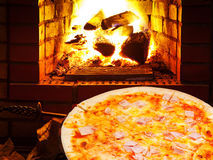Pizza with prosciutto cotto and open fire in oven Stock Photos
