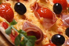 Pizza with prosciutto ham, tomatoes, black olives macro texture Royalty Free Stock Images