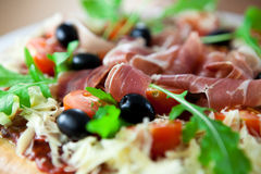 Pizza with prosciutto and olives royalty free stock photo