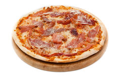 Pizza with prosciutto on wood plate Royalty Free Stock Images