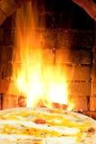 Pizza quatro formaggi and fire flames in oven Stock Photo