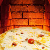 Pizza quatro formaggi and hot brick oven Royalty Free Stock Images