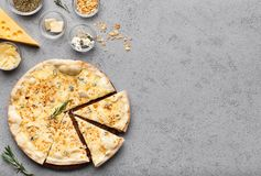Pizza quattro fromaggi cutted into slices, top view. Pizza quattro fromaggi cutted into slices on grey table, top view stock images