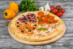 Pizza in quattro parti, con i rosmarini e le spezie su un fondo di legno leggero immagini stock