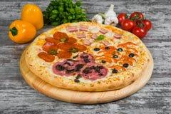 Pizza in quattro parti, con i rosmarini e le spezie su un fondo di legno leggero fotografia stock