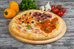 Pizza in quattro parti, con i rosmarini e le spezie su un fondo di legno leggero fotografie stock libere da diritti