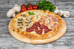 Pizza in quattro parti, con i rosmarini e le spezie su un fondo di legno leggero immagine stock libera da diritti