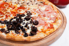 Pizza Quattro Stagioni on a wood plate Stock Photo