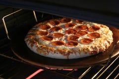 Pizza que cocina en piedra Foto de archivo libre de regalías