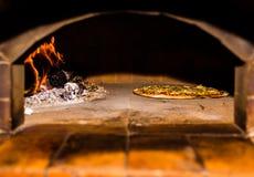 Pizza que cuece en el horno de madera del ladrillo con leña y la llama Fórmula hecha en casa y original de It's para cocinar la foto de archivo libre de regalías