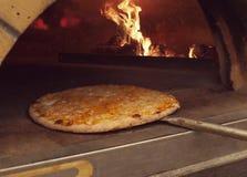 Pizza que entra el horno Fotografía de archivo libre de regalías