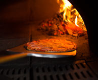 Pizza que obtém do forno Fotos de Stock Royalty Free
