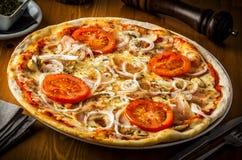 Pizza quente com cogumelos, bacon, tomate e cebolas imagem de stock royalty free