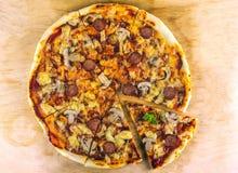 A pizza recentemente cozida com salame, mexilhões e cogumelos, fritou o pi Foto de Stock