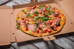 Pizza recentemente cozida Picante, meaty, pizza de queijo em uma caixa da caixa Pizza em um fundo cinzento Conceito da entrega da foto de stock
