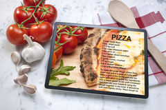 Pizza Recipe Tablet Food. A tablet computer with a pizza recipe on the screen. With tomatoes, garlic, wood spoon and tea towel Royalty Free Stock Images