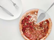 Pizza with red tomatoes, mozzarella cheese on top of a white table stock image