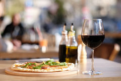 Pizza and red wine in restaurant Stock Images
