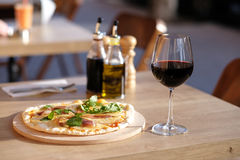 Pizza and red wine in restaurant Royalty Free Stock Photography