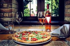Pizza and red wine on the table stock photo