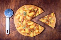 Pizza redonda con queso cortado con un cuchillo con un pedazo fotografía de archivo libre de regalías