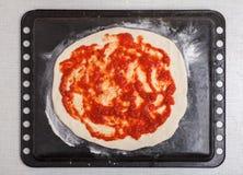 Pizza redonda del ra con la salsa de tomate en la bandeja de la hornada Imágenes de archivo libres de regalías