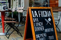 Pizza restaurant `La fucina`, Javastraat street, Amsterdam, Netherlands. View of advertising board against outside tables and chai. Rs royalty free stock photo