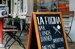 Pizza restaurant `La fucina`, Javastraat street, Amsterdam, Netherlands. View of advertising board against outside tables and chai. Rs royalty free stock photography